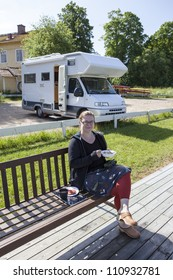 Woman eating breakfast outdoors in fron of her camping car. She has a pair of binoculars on her knees.