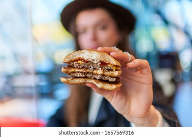Woman eating burger bun with beef in fast food restaurant
