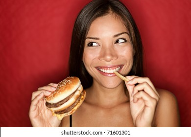 Woman eating burger and fries smiling. Beautiful mixed race asian caucasian female model on red background.