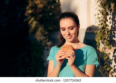 Woman Eating Burger Outdoors on the Street. Gourmand lady having a hamburger to go