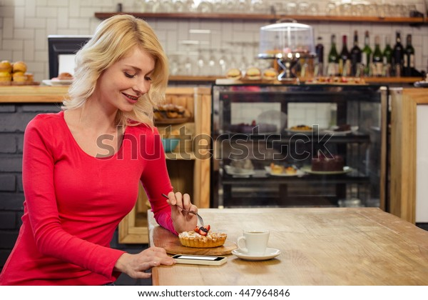 Woman eating a cake alone in a cafe