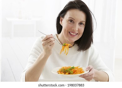 Woman eating a carrot salad.