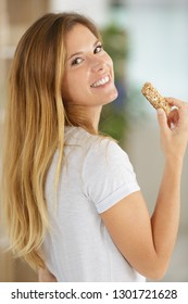 woman eating a cereal bar indoor