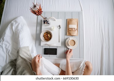 Woman eating cereals in bed, light background