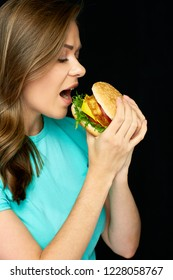 Woman eating cheeseburger, isolated portrait on black.