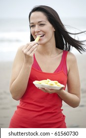Woman eating chips at the beach