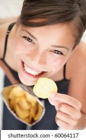 Woman eating chips. Beautiful young woman eating potato chips / crisps.