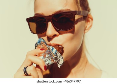 Woman eating chocolate. Beautiful young woman sitting on the coach and eating chocolate, Hipster girl, health foo, sweet, tasty, sunglasses