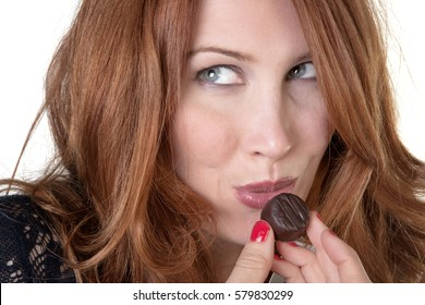 woman eating chocolate from a large chocolate box