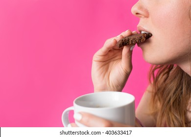 Woman eating cookie with cup of coffee in her hands