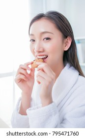 Woman eating cookie at home