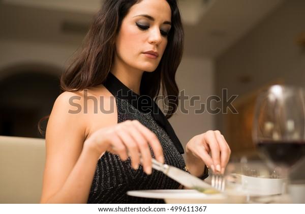 レストランで夕食を食べている女性