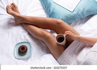 Woman eating a donut in the bed