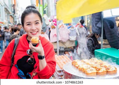 Woman eating Egg bread with almond, peanut and sunflower seed at Myeong-dong street food, Seoul, South Korea