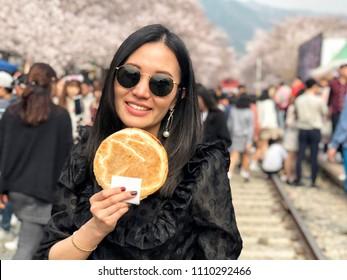 Woman eating Egg bread dessert at Jinhae Gunhangje Festival street food in Seoul, South Korea