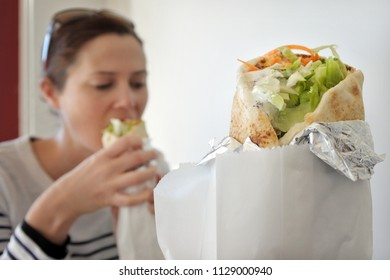 Woman eating falafel warp. Food background and texture.
