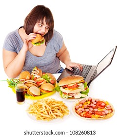 Woman eating fast food at working pc. Isolated.