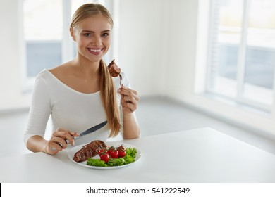 Woman Eating Food. Beautiful Smiling Female Having For Dinner Delicious Grilled Meat With Fresh Vegetables In Kitchen. Healthy Attractive Girl Dining Having Beef Steak With Tomatoes, Salad. Nutrition