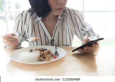 Woman Eating food while Checking her smartphone in a Restaurant. Technology addict using Smartphone in the meal time