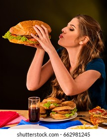 Woman eating french fries and hamburger with pizza. Student consume fast food on table. Girl trying to eat junk on dark background. Cook teaches cook and shares recipes. Girl suffering from gluttony.