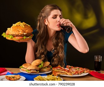 Woman eating french fries and hamburger with pizza. Portrait of student consume fast food on table. Girl trying to eat junk on dark background. Disruption from diet.