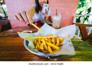 Woman eating french fries while using smart phone.