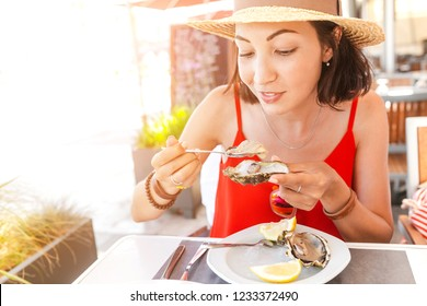 woman eating fresh oyster in seafood mediterranean restaurant