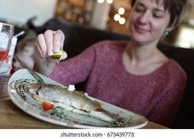 Woman eating fried trout in a restaurant