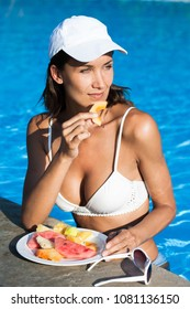 woman eating fruit at the edge of a pool