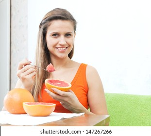 Woman eating grapefruit with spoon at home