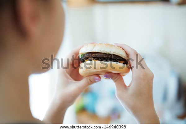Woman eating hamburger. Rear view