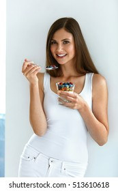 Woman Eating Healthy Diet Food. Portrait Of Beautiful Happy Young Female Holding Glass Of Natural Yogurt, Berries And Oats. Smiling Girl Having Yoghurt Oatmeal Dessert For Breakfast. High Resolution