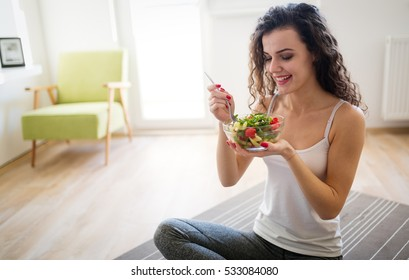Woman eating healthy salad after working out at home