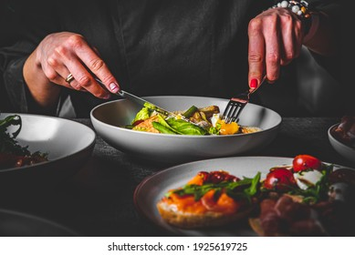 woman eating healthy salad from bowl sitting in cafe