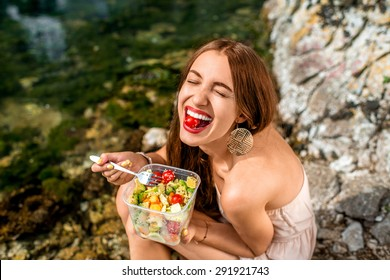 Woman eating healthy salad from plastic container near the river
