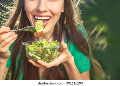 Woman eating healthy salad from plastic container over green grass with flying hair on a sunny spring day. backlight