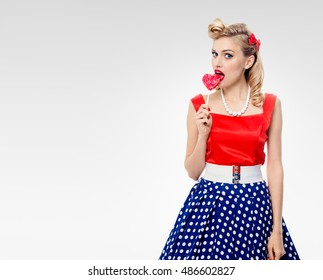 Woman eating heart shape lollipop dressed in pinup style dress in polka dot, on grey with blank copyspace area for text or slogan. Caucasian blond model in retro fashion, vintage concept studio shoot.