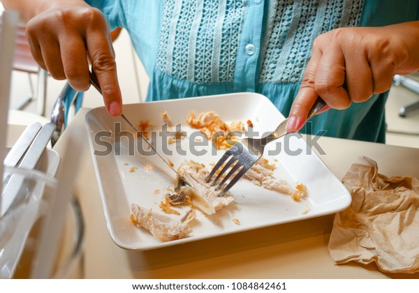 The woman is eating her food by using knife and fork.