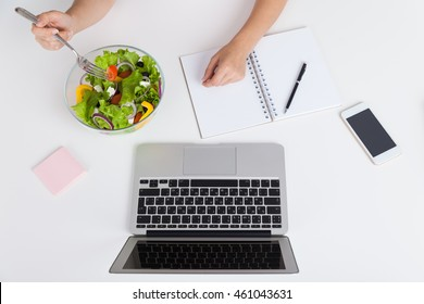 Woman eating her lunch in office. Bowl of vegetable salad, laptop, cell phone and notebook on table. Concept of lunch break at busy office and healthy food. Top view