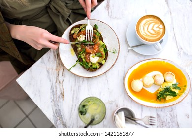 Woman eating her tasty brunch on hipster cafe, top view of marble table, salmon avocado toast , coffee and sweet tasty cheesecakes, enjoying her breakfast.