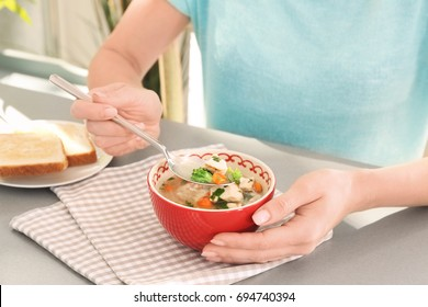 Woman eating homemade chicken soup on table