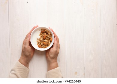 Woman eating homemade granola breakfast cereals with mixed nuts, oats and Greek yogurt in bowl. Female hands holding healthy vegetarian food with cashew, almond, hazelnut. Morning light, copy space.