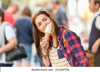 Woman eating Ice cream on vacation travel. Smiling girl having fun eating icecream outdoors during holidays in Europe.