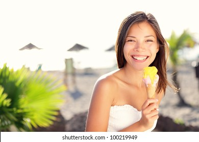 Woman eating ice cream outside on summer vacation in holiday beach resort. Happy mixed race girl in her twenties