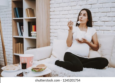 Woman is Eating a Ice Cream with Spoon. Woman is a Young Brunette Pregnant Girl. Girl Sitting on Couch. Woman is Thinking. Different Food and Cola on Table. Person Located at Home.