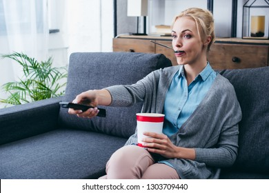 woman eating ice cream while siitng on couch and wathicng tv at home alone