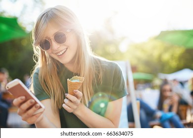 Woman eating icecream using smartphone. Portrait of a girl with ice cream browsing through social media or messaging her friends enjoying summer in the city park.