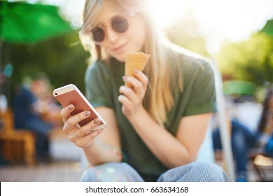 Woman eating icecream using smartphone. Portrait of happy girl with ice cream browsing through social media or messaging her friends enjoying summer in the city park wearing shades. Focus on phone.