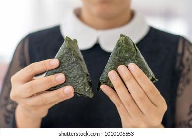 Woman eating japanese rice cake, onigiri on seaweed