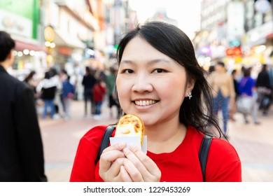 Woman eating Korean egg cake food street in Hongdae shopping street in Seoul, Korea